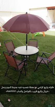 طاولة مع اربع كراسي ومظلة شمسية شبه جديدة